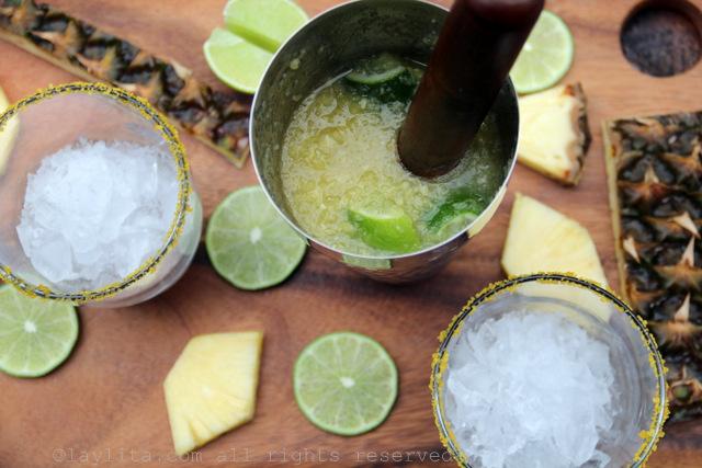 Aplaste los limones con el azucar, y agregue la cachaza y el pure de piña