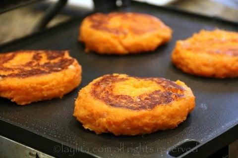 Cocine los llapingachos en una plancha o parrilla plana hasta que esten dorados por ambos lados