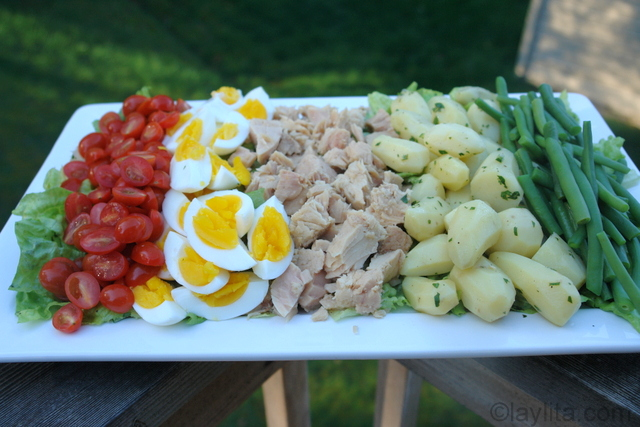 Poner los tomates, huevos duros, atun, papas y vainitas encima de la lechuga
