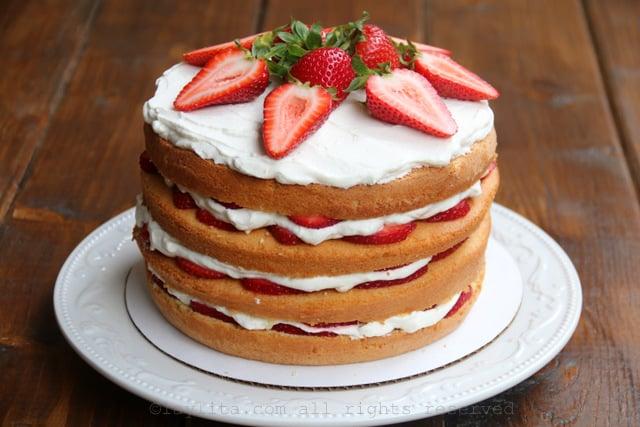 Para la capa final del pastel, cubrala con la crema batida y decore con las fresas reservadas