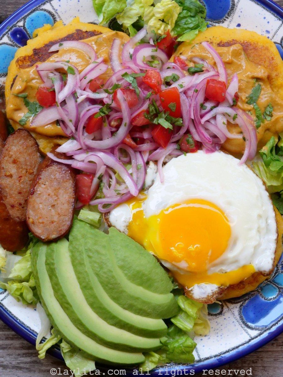 Llapingachos o tortillas de papa con salsa de mani, curtido, huevo frito, aguacate y chorizo
