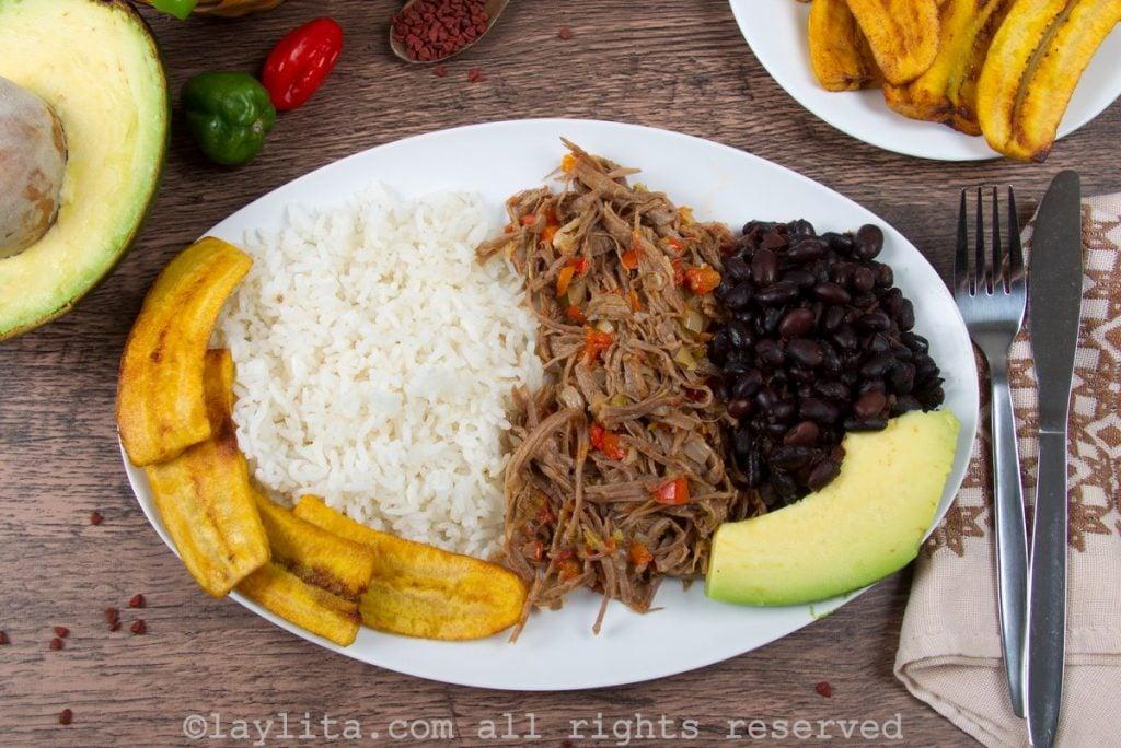 Pabellón venezolano con caraotas negras, carne mechada, arroz, tajadas y aguacate