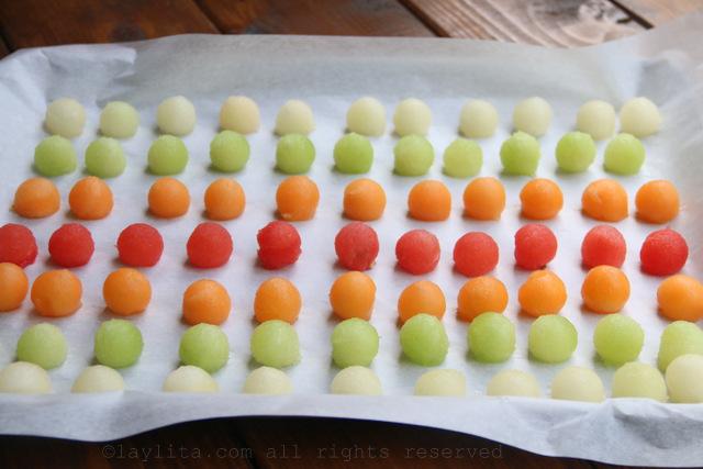 Ponga las bolitas de melon en una bandeja forrada con papel pergamino o papel encerado