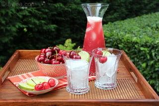 Sirva la limonada con hielo y decorada con rodajas de limon cerezas