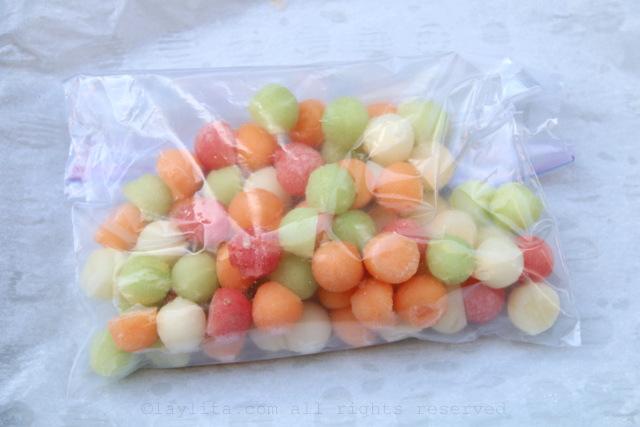 Transfiera las bolitas de fruta congelada a una funda o bolsa de plastico y guardelas en la congeladora o nevera hasta el momento de usarlas.