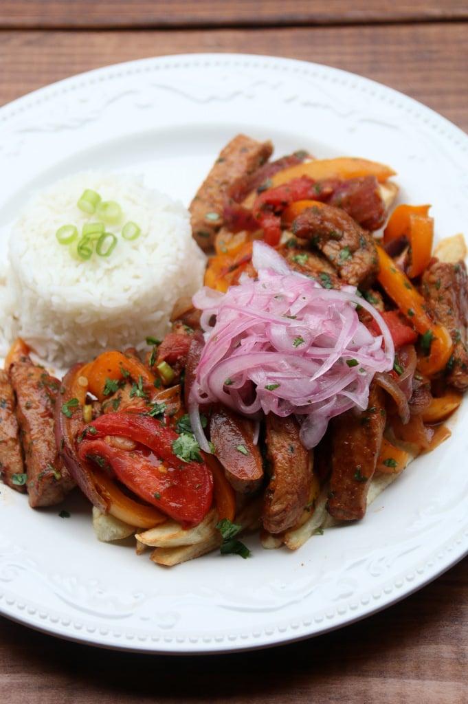 Lomo saltado de cerdo con papas fritas, arroz y curtido