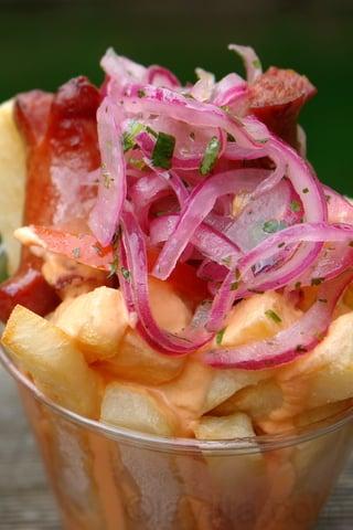 Salchipapas con curtido de cebolla y tomate