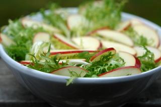Fines tranches de pommes sur la salade frisée