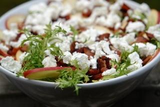 On ajoute le fromage de chèvre en petits morceaux sur la salade frisée