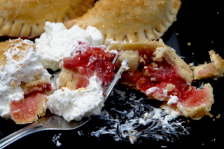 Strawberry and rhubarb empanadas with whipped cream