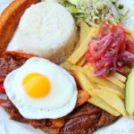 Ecuadorian churrasco plate: steak with fried egg, rice, fries, salad, avocado, and plantains