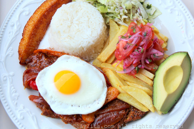 Ecuadorian churrasco plate: steak with fried egg, rice, fries, salad, avocado, and plantains