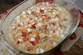 Cubra el pescado con el jugo de limon, ajies o chiles picados, y cilantro picado
