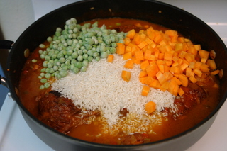 Add the broth, rice, peas and carrots
