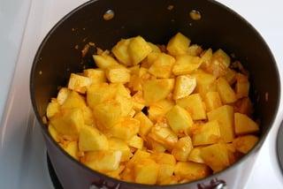 Acrescente as batatas à panela e misture bem até que estejam revestidas com a fritada. Continue cozinhando por mais 5 minutos, mexendo a cada dois minutos mais ou menos.