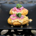 Stuffed hominy patties with peanut sauce, pickled onions and aji sauce
