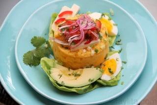 Purée de pomme de terre avec des avocats, une sauce aux oignons et aux tomates, du fromage frais et des œufs durs.