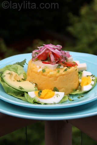 Molo équatorien ou purée de pommes de terre avec du fromage frais, des avocats, des œufs durs et une sauce tomate aux oignons