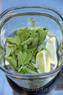 Coloque os pedaços de limão ou de lima com a hortelã, o mel, um pouco de gelo e água no liquidificador