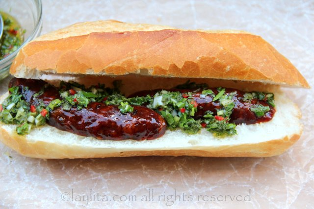 Easy recipe for choripan: Place the grilled chorizo on the bread and top with chimichurri