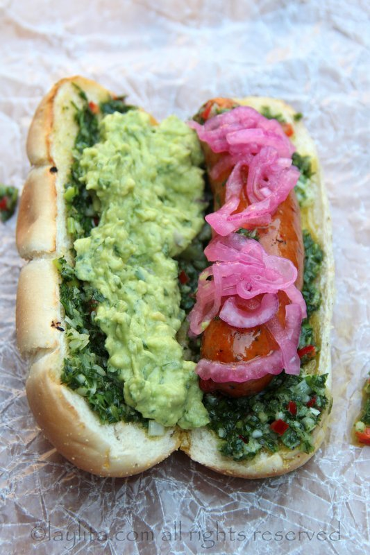 O cachorro-quente latino completo: choripan com cebolas roxas e guacamole