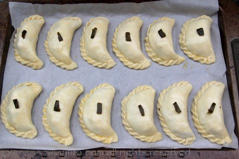 To differentiate the empanadas, you can add a small piece of the filling to the top