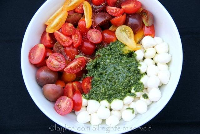 Mezcle los tomates con las perlitas de queso mozzarella y la salsa de albahaca