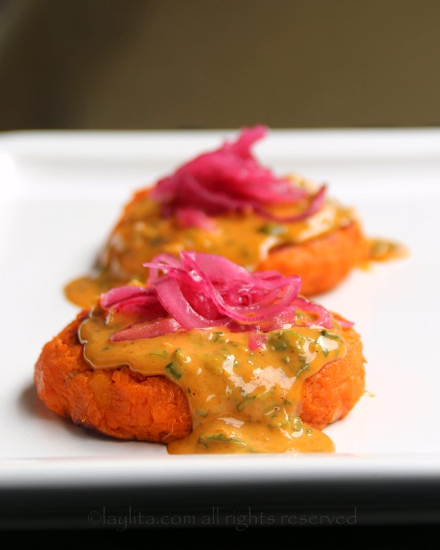 Sweet potato patties topped with peanut sauce and pickled red onions