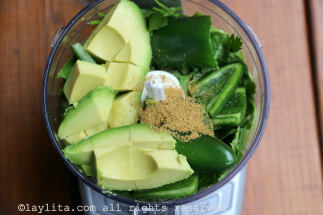 Place the avocado pulp, the chopped cilantro, jalapeño peppers, green onions, cumin powder, and lime juice in a small food processor or blender.
