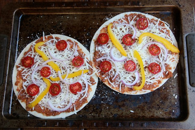 Veggie tortilla pizza with bean sauce, cheese, tomato, onion and bell pepper