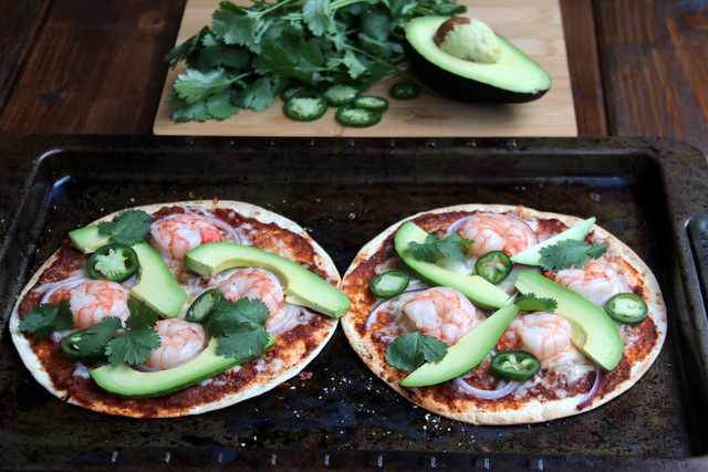 Top the baked tortilla pizzas with avocado slices and fresh cilantro