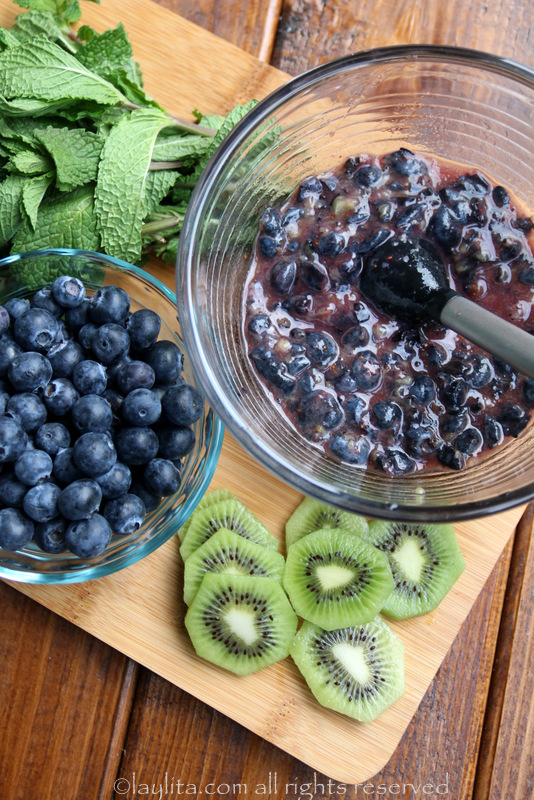 Crush half of the blueberries with a muddler