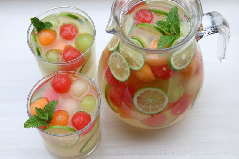 Melon sangria garnished with lime slices and mint leaves