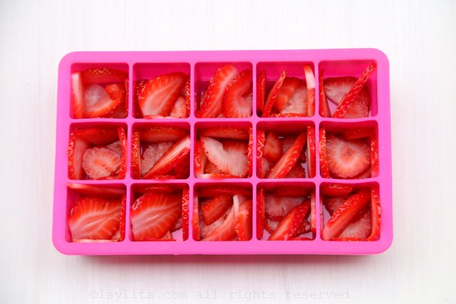 Arrange the sliced strawberries in the ice cube tray