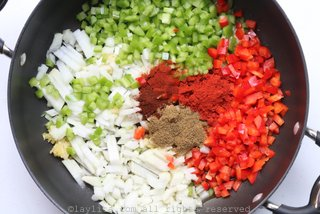 Cook the diced onions, bell pepper, crushed garlic with oil and spices to make a refrito or sofrito