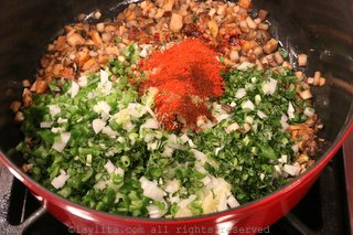Add the chopped onions, garlic, jalapenos, paprika, cumin, and other spices