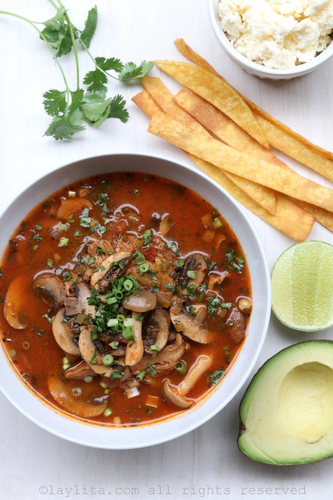 Spicy mushroom tortilla soup with avocado, queso fresco, tortilla chips, and lime