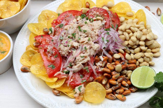 Arrange the plantain chips, the corn nuts, and the lupini beans on a plate, then top with the tomato, onion, and tuna fish mix