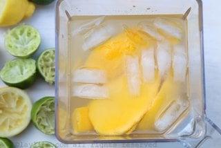 Ponga los pedazos de mango, el jugo de limón, la azúcar o miel, 2 tazas de agua, y unos cubitos de hielo en una licuadora.