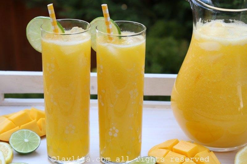 Sirva el refresco o limonada de mango con hielo al gusto, decore los vasos con hojitas de menta fresca y rodajas de limón.