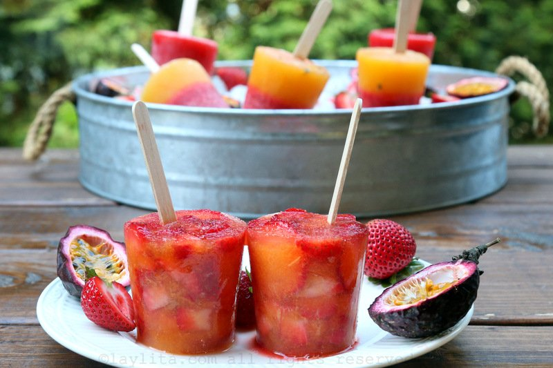 Popsicles or paletas made with chopped strawberries and passion fruit juice