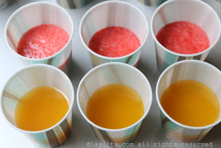 For the layered popsicles, fill each cup about half full with strawberry or passion fruit mix