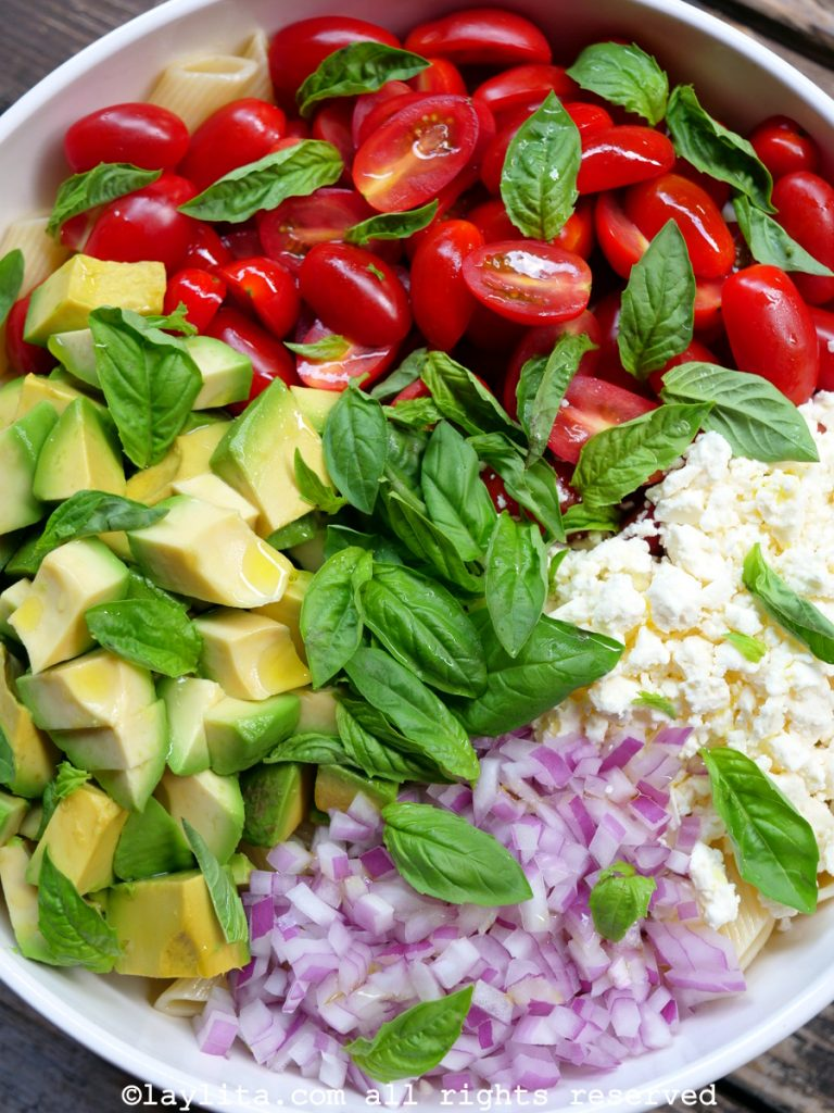 Pasta salad with avocado, tomato, red onions, feta, and basil