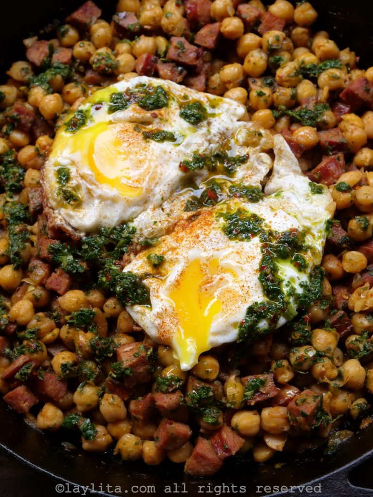 Garbanzos or chickpeas with chorizo and chimichurri - topped with fried eggs